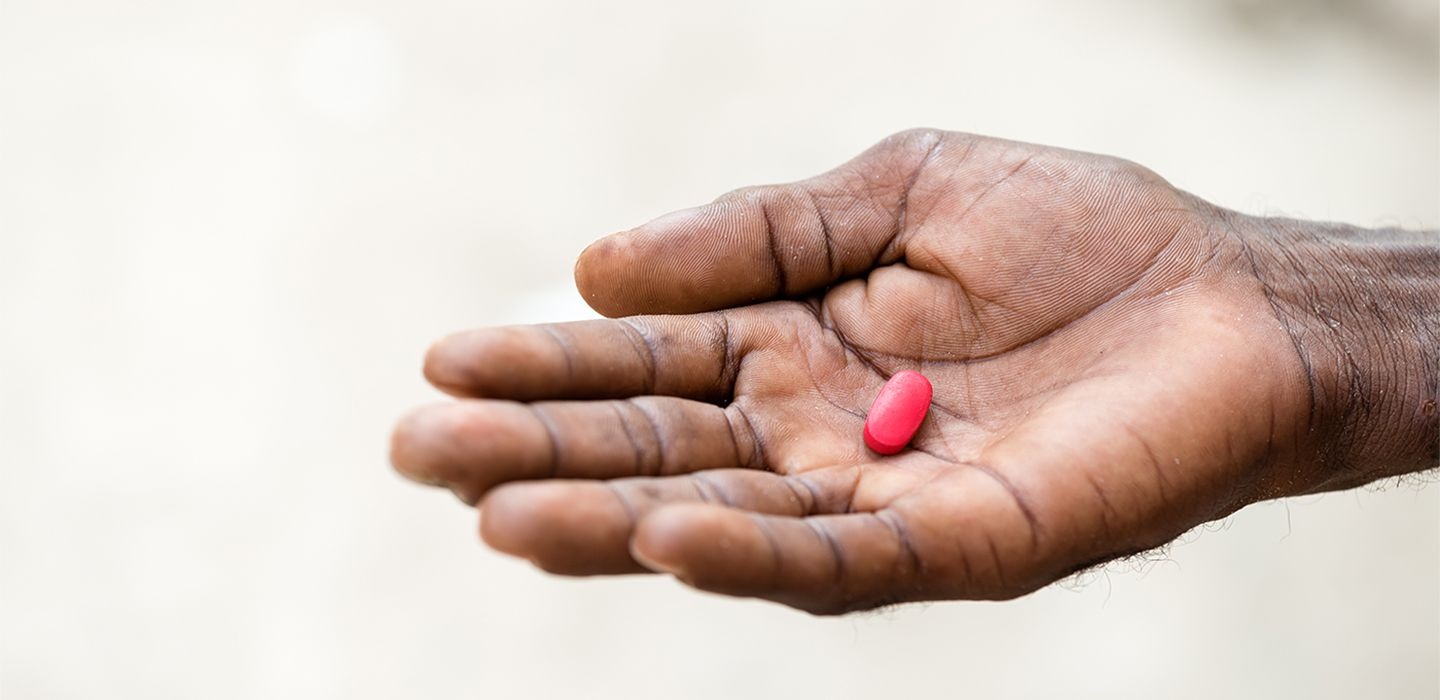 Red oval pill resting in palm of hand