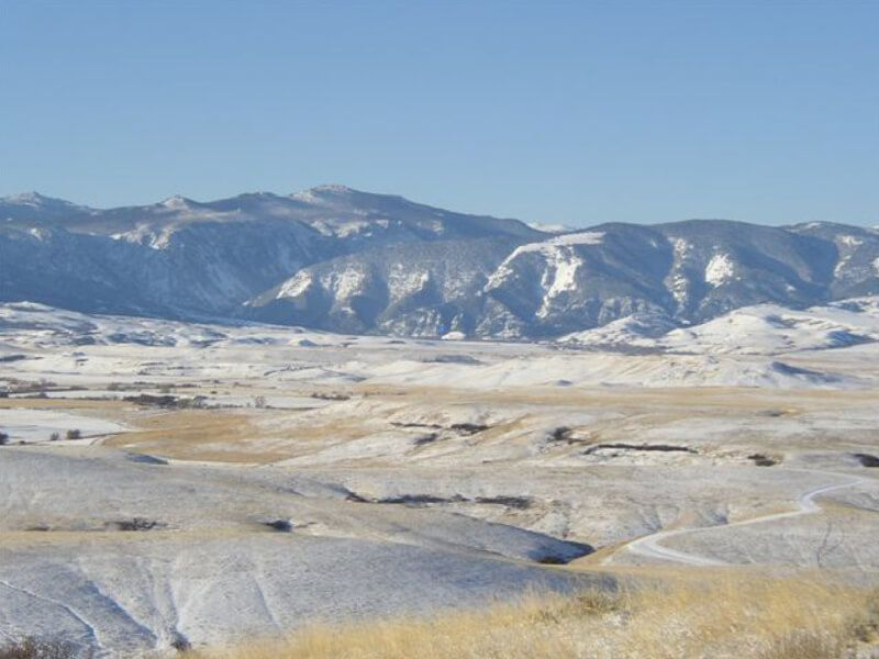 Flat coal bed methane fields of the Powder River Basin in Wyoming, with snowy mountains in the distance