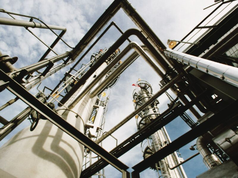 Outdoor view of a chemical and petrochemical plant with pipes, tanks, and towers shot from below