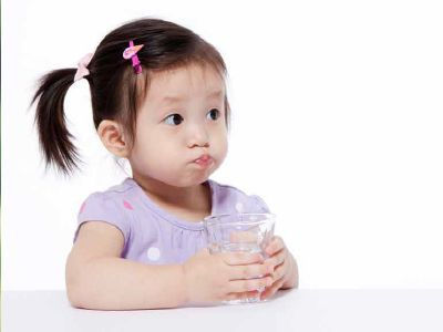 Toddler with pigtails and puffed-out cheeks holds a glass containing clean, safe drinking water