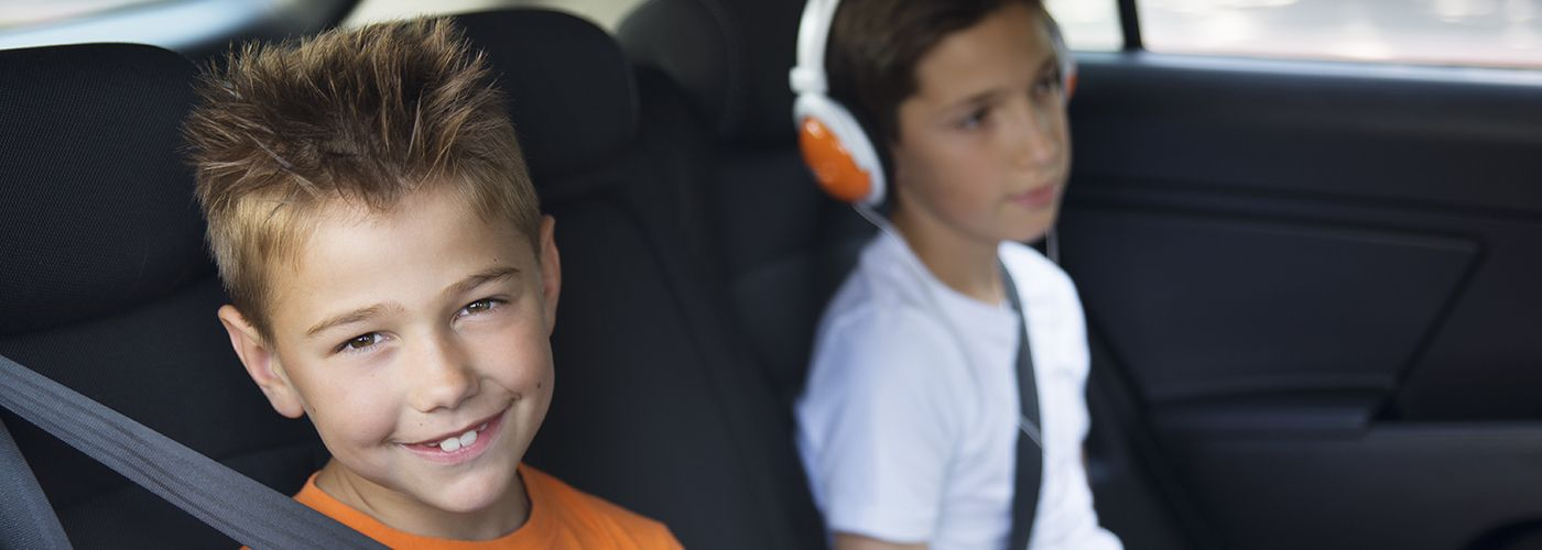 Two young boys sitting  in a car  playing tablet and smart phone