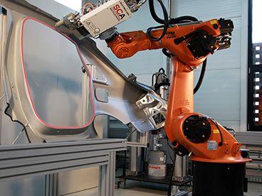 Orange robot applying adhesive