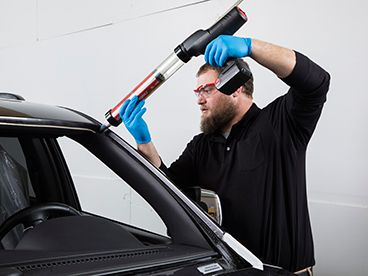Technician applying BETASEAL to windshield area