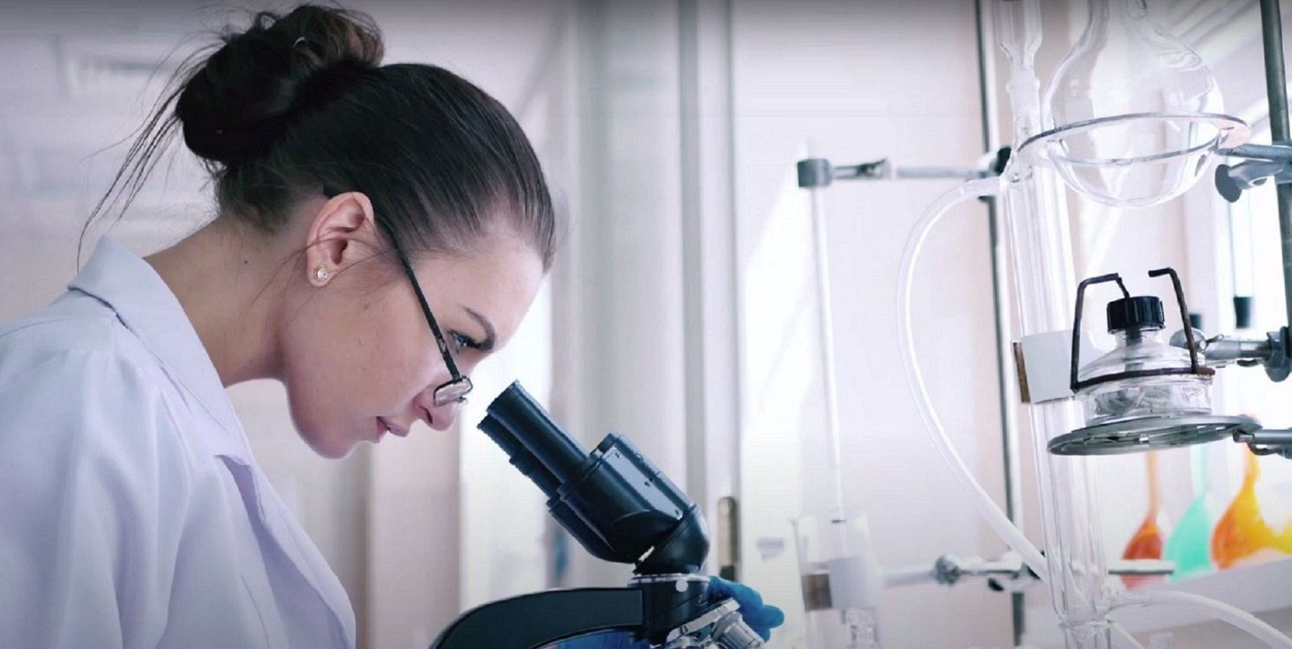 Bioprocessing with gloved worker using microscope