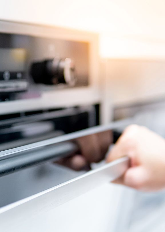 Person opening an oven door made with polymers that replace metal.