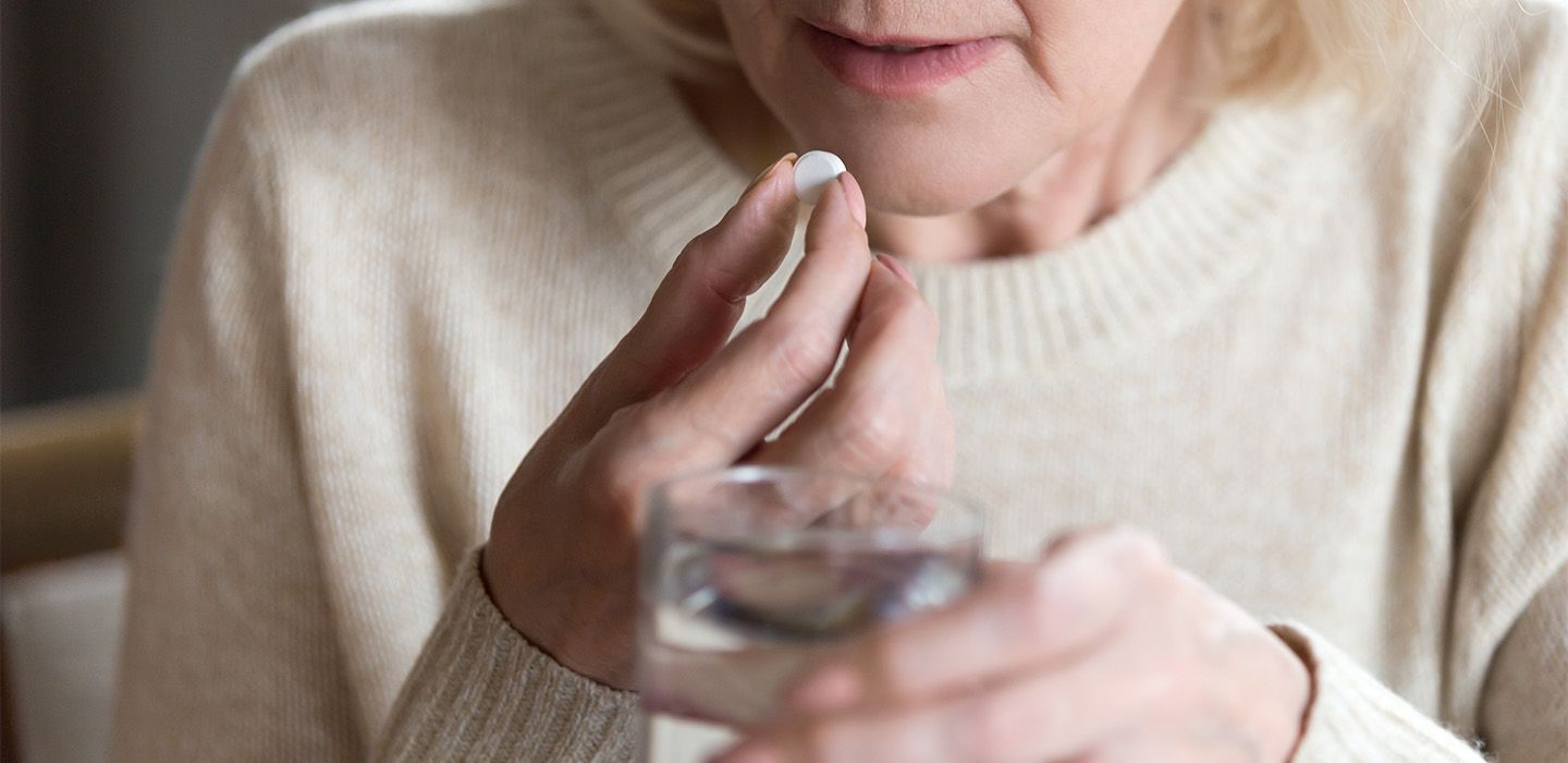 Woman about to take a dissolving tablet with a glass of water.