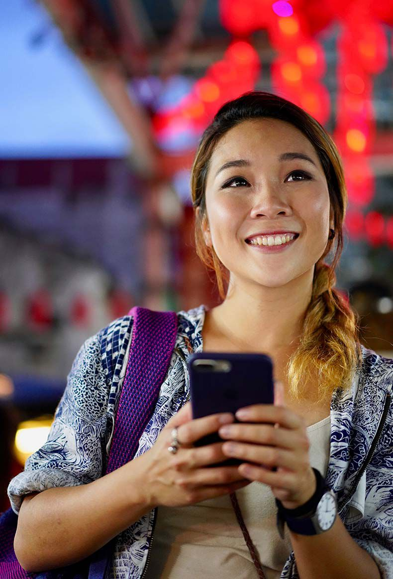 Smiling woman holding a smartphone symbolizing evolving electronic connector technology