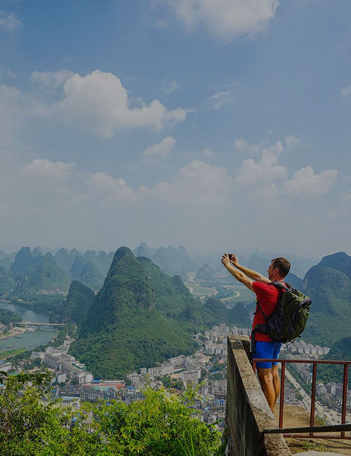 Man with backpack taking scenic picture with smartphone as an example of electrical technologies from DuPont
