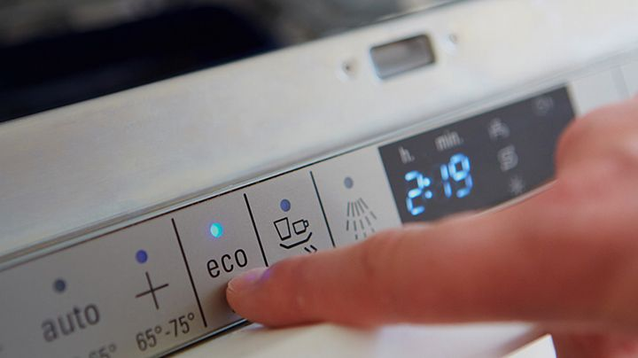 Washing machine control panel with its economy modebuttonbeing pressed, showing DuPont consumer product solutions in action
