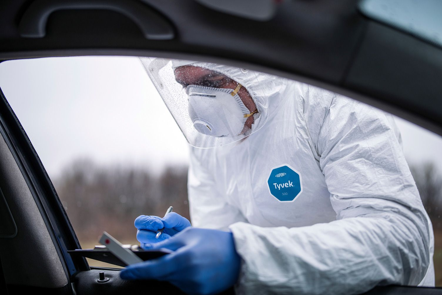 Man with protective suit wearing full protective suit, he giving fast COVID-19 test on border, he doing border traffic control because of Coronavirus pandemic.