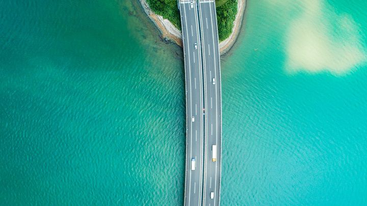 Cars going across a bridge over large body of water
