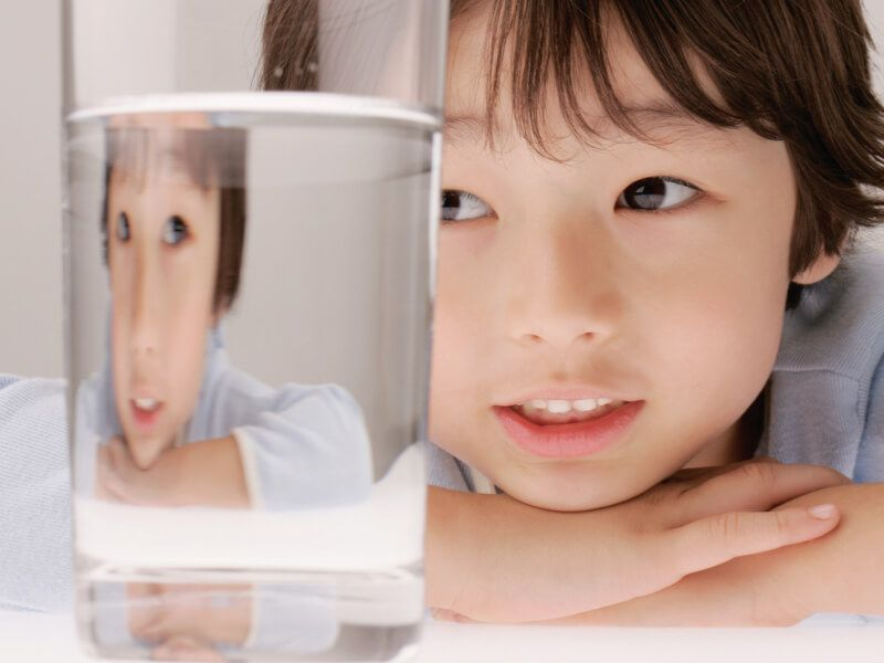 Young boy looking through a glass containing clean, clear household water