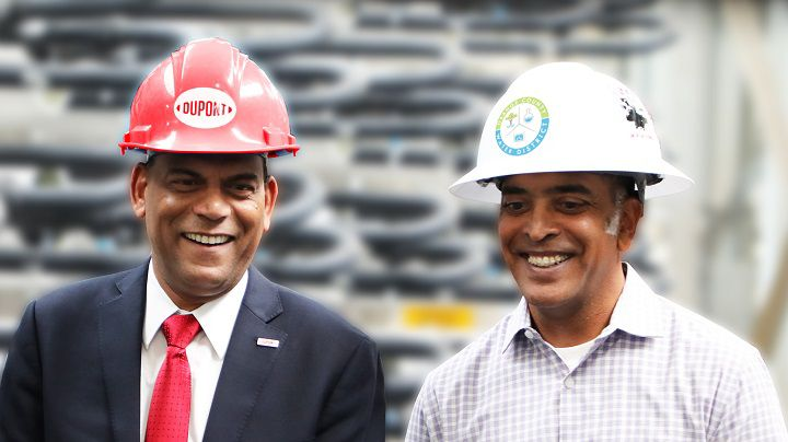 Two men in hardhats walking through a water treatment plant