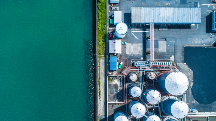 Aerial view of a chemical processing & catalysis facility requiring water treatment next to a flowing river.