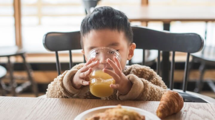 Young boy sitting at a table for his breakfast food and beverage, sipping a glass of orange juice.