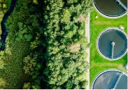 Aerial view of a municipal water treatment plant's settling tanks next to a dense bank of trees and a brook