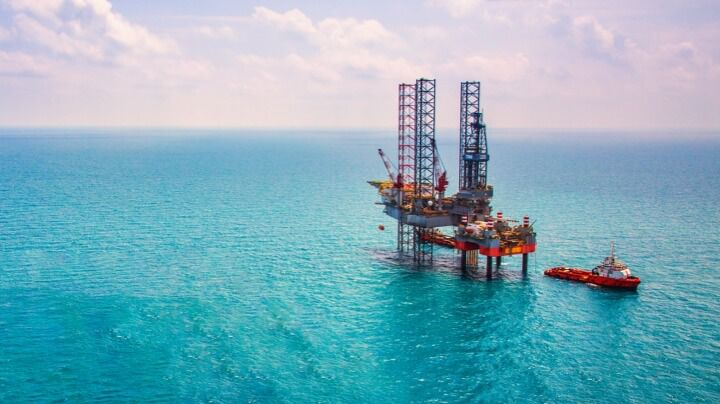 Offshore rig and red-hulled boat for the oil and gas industry in a bright blue sea