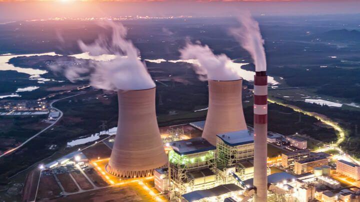 夕阳下灯火通明的核电厂鸟瞰图,远处是河流和城市