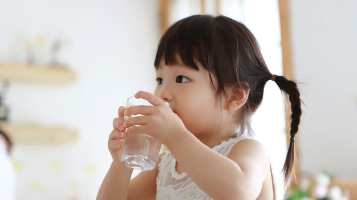阳光明媚的房间里,小女孩喝着满满一杯安全干净的饮用水。