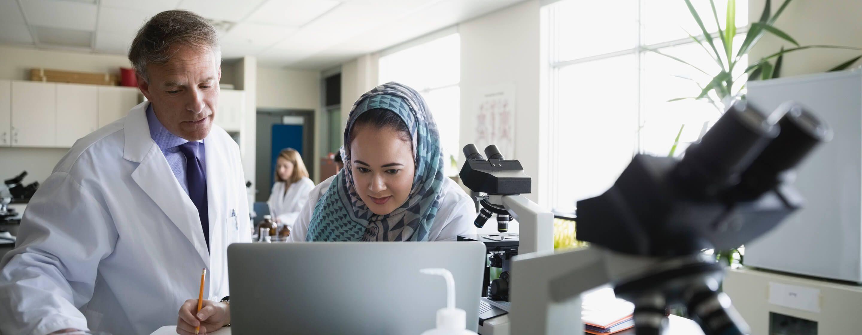穿着白色实验服的男人和女人在实验室里的电脑和显微镜前工作,他们身后是另一个女人