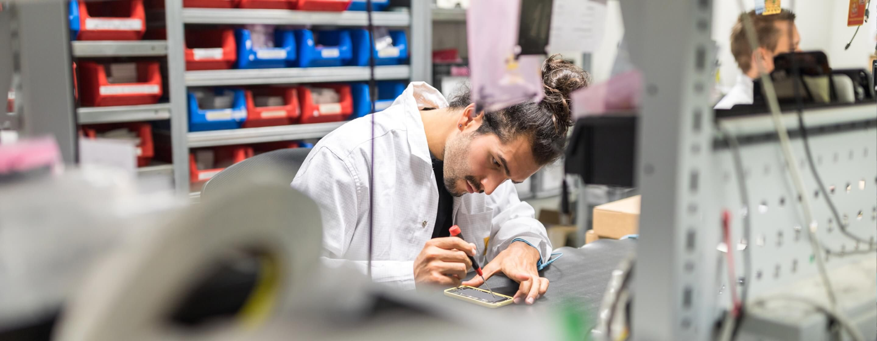Man in white lab coat concentrating on soldering a mobile phone in the microelectronics industry