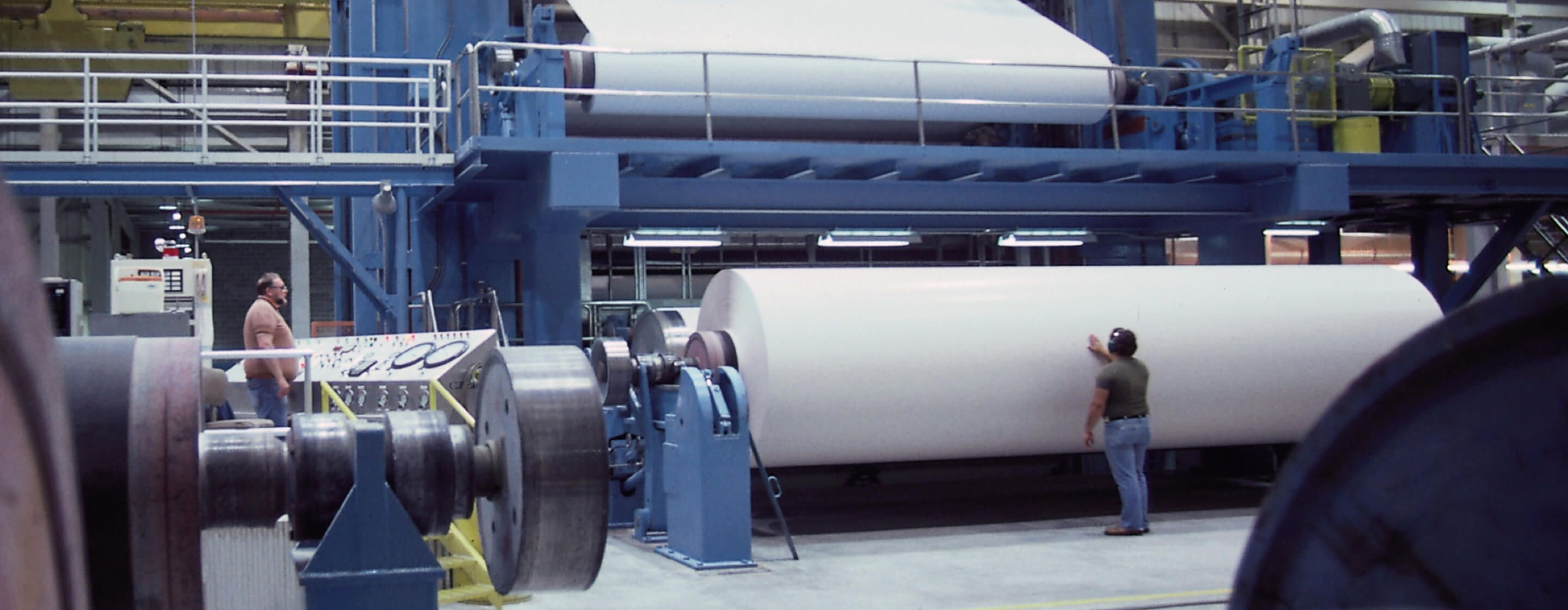 Man inspecting massive roll of paper in a pulp and paper plant