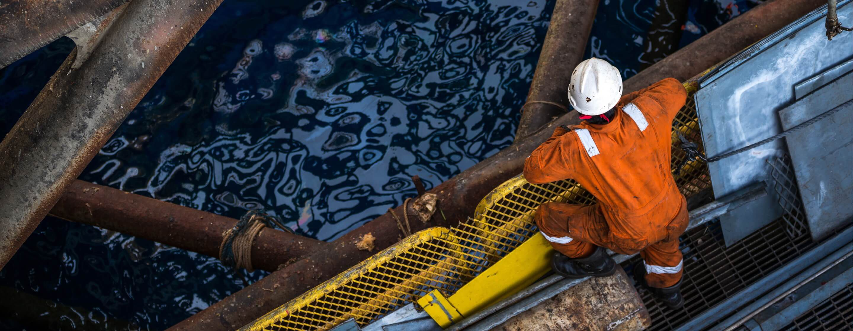 Overhead view of an offshore oil-rig worker in a jumpsuit, hard hat, and work boots looking down into ocean water