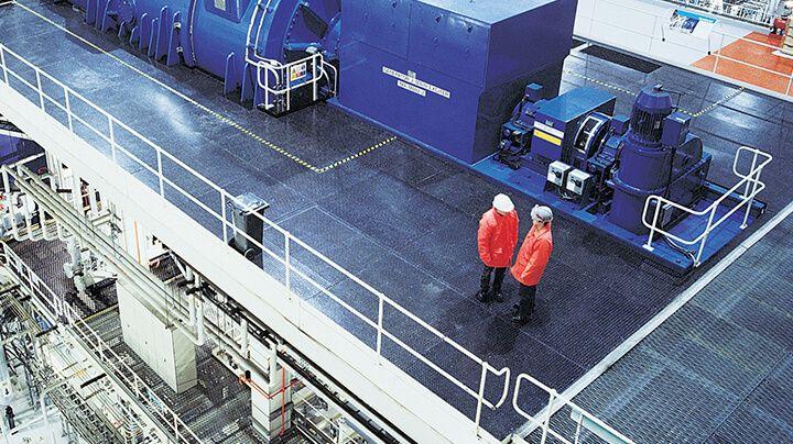 戴着安全帽、身穿橙色夹克的两个人在一处大型多层工业设施顶层交谈的俯视图。