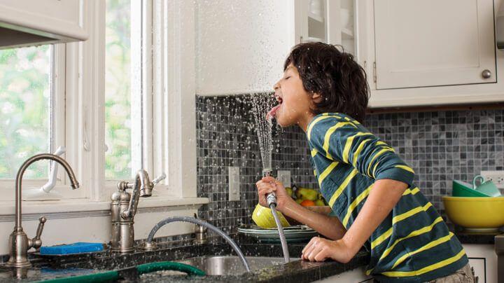 男孩从厨房水槽的喷头喝干净的家庭用水。