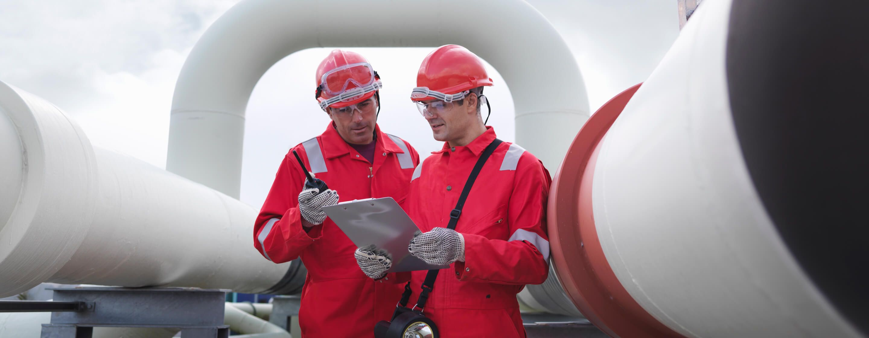 Two engineers in red jumpsuits and hard hats looking at a clipboard in an outdoor area of a power generation plant