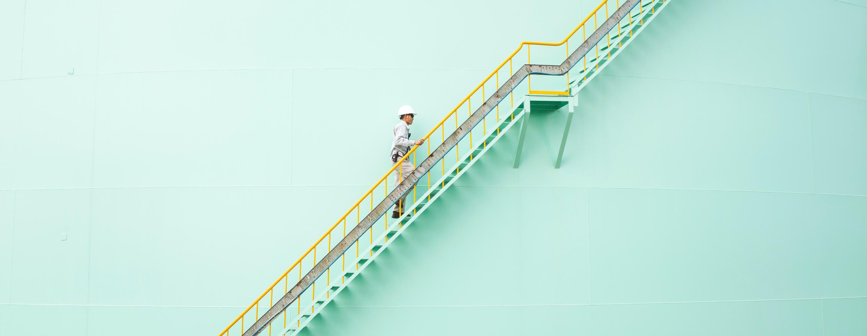 戴着安全帽的工人走在一个巨大的浅绿色化工和石化罐侧面陡峭的楼梯上