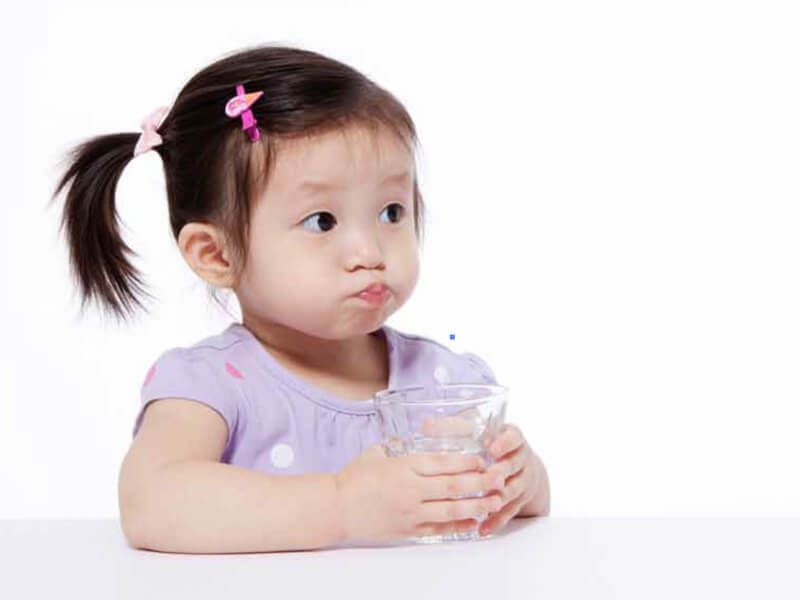 Toddler girl with ponytails and puffed-out cheeks holds a clear glass of clean drinking water