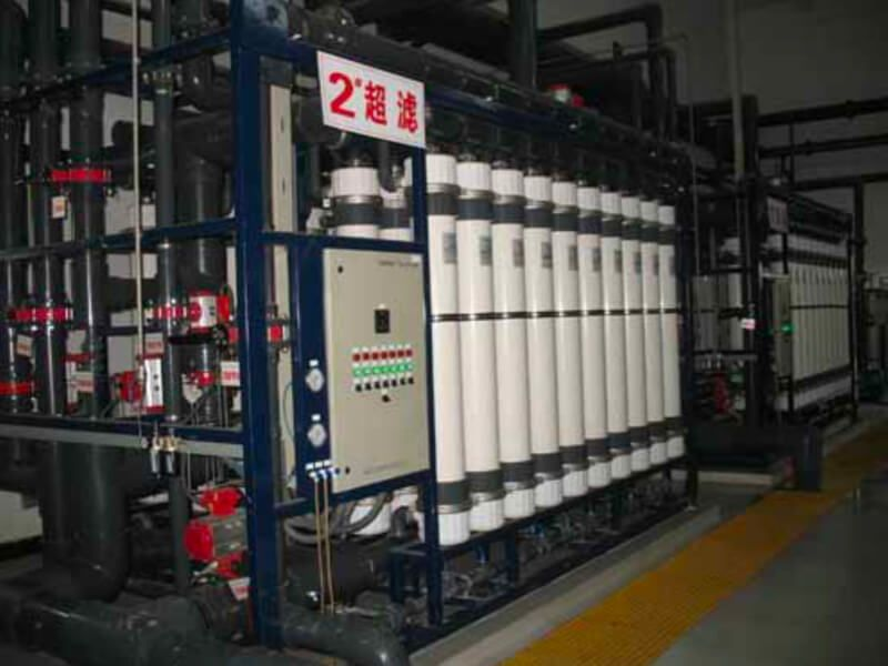 Two side-by-side ultrafiltration skid installations in a cogeneration power plant, with a sign with red Chinese characters